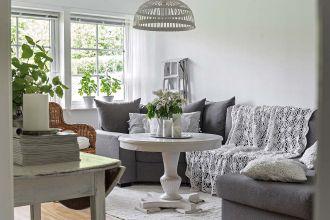 Białe wnętrza szwedzkiego domu wśród starych jabłoni