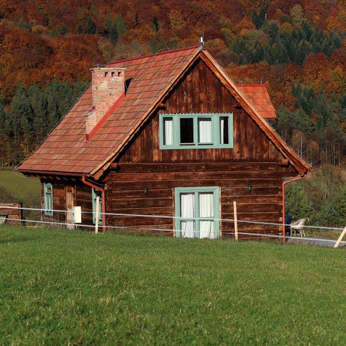Beskid Niski: drewniana chatka z miętowymi oknami i łemkowskim akcentem