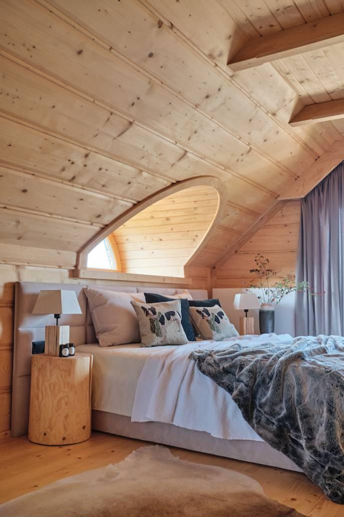 Sypialnie na poddaszu mają charakterystyczne półokrągłe okienka. Lniane poduszki i pościel w barwach ziemi tworzą przytulny klimat ze świerkowymi meblami.