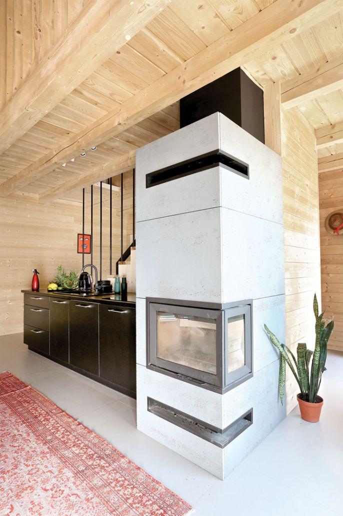 Pośrodku domu stoi prosty betonowy kominek ogrzewający cały dom.