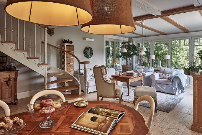 W salonie Monika połączyła kanapy i fotele z IKEA z antycznym wiejskim stolikiem i regałem ze skrzynek po winie.  Wysokie okna i dywan z motywem koniczyny marokańskiej to ukłon w stronę stylu Hampton, który bardzo lubi.