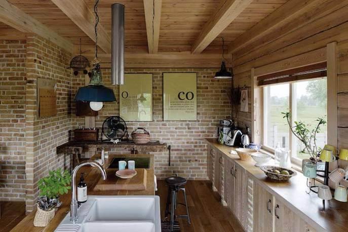 Murowane szafki, drewniany blat, fronty z desek. Uchwyty i stołek barowy marki Rustykalne Uchwyty.