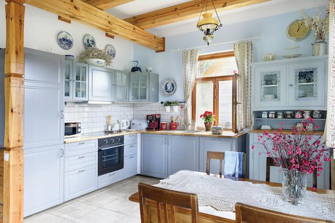 Meble z IKEA, a do tego stary stół, żyrandol, porcelanowe talerze  na ścianie i koronkowa serweta – przytulna kuchnia z nutą nostalgii.